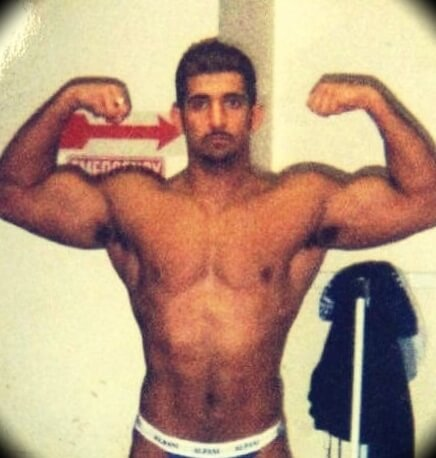 A younger Patrick Bet-David doing some bodybuilding poses for the camera